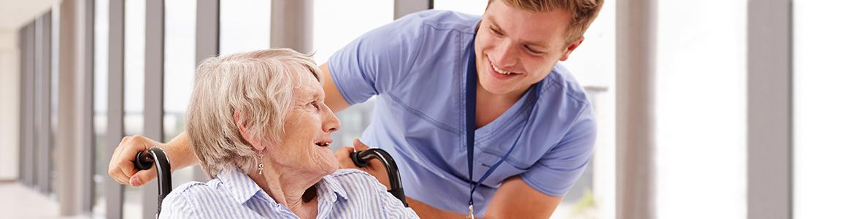 13114212-nurse-pushing-senior-patient-in-wheelchair-along-corridor.jpg