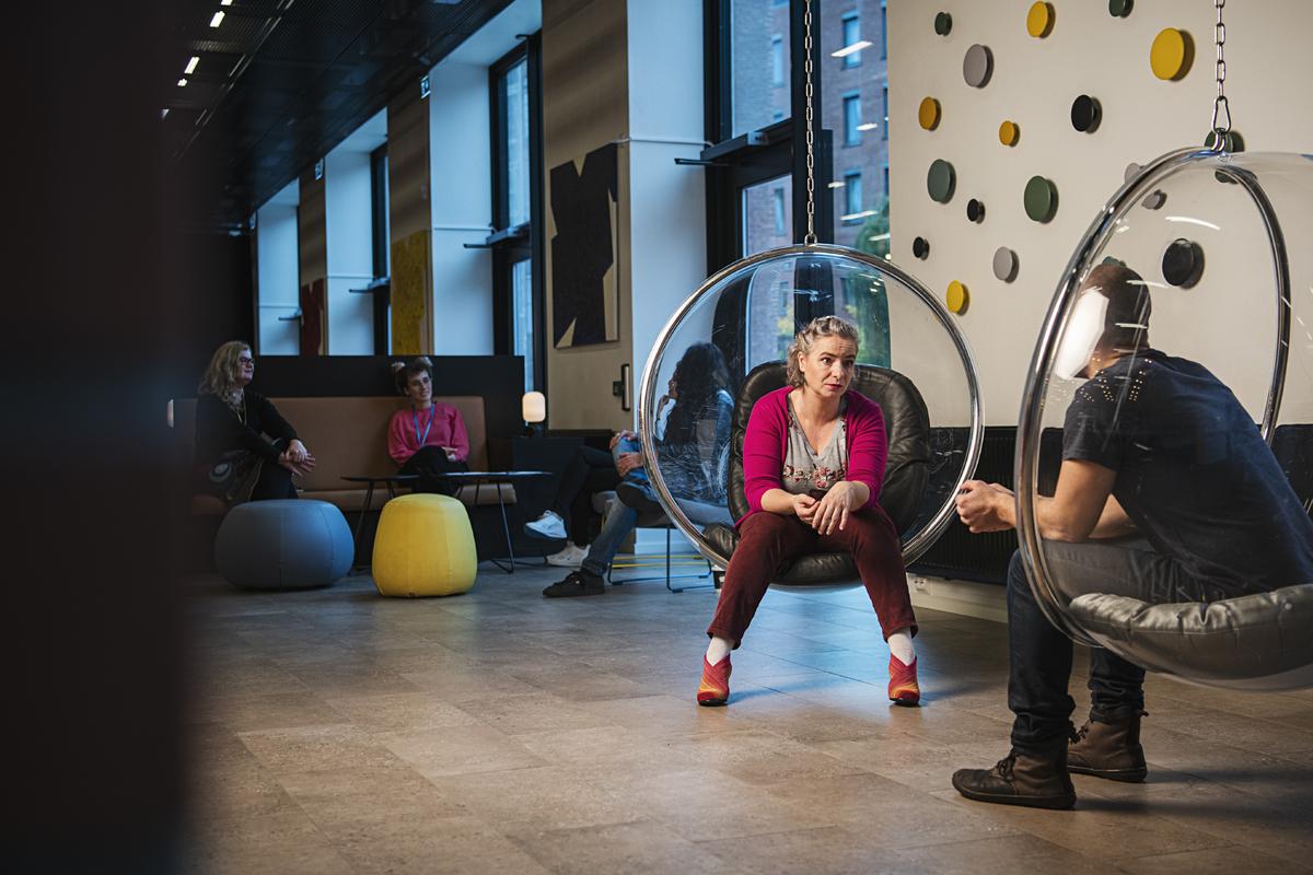 To kolleger i samtale i studiehallen sittende i runde design stoler formet som glasskuler