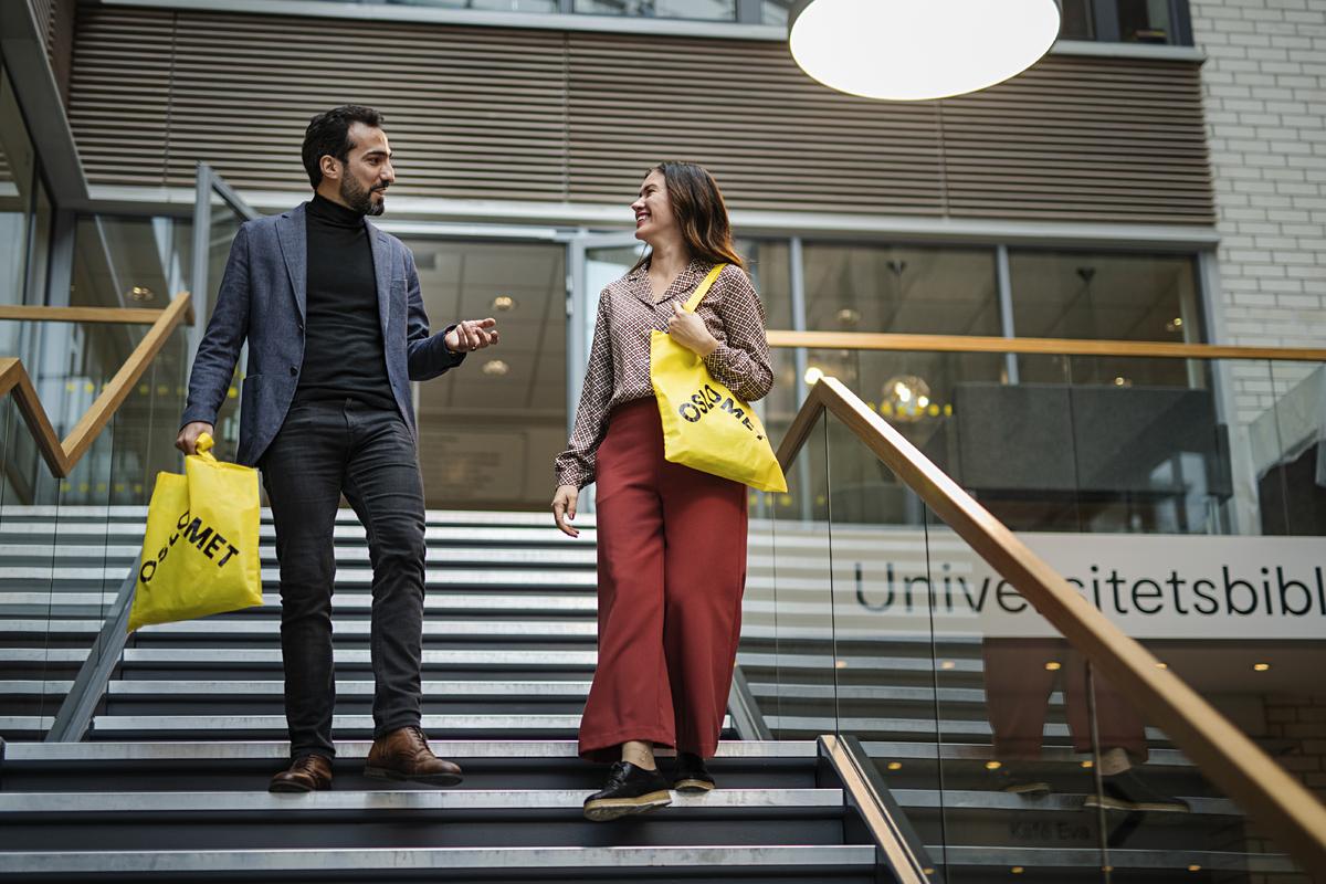 Mann og dame i samtale vandrer ned trappa ved biblioteket med gule poser