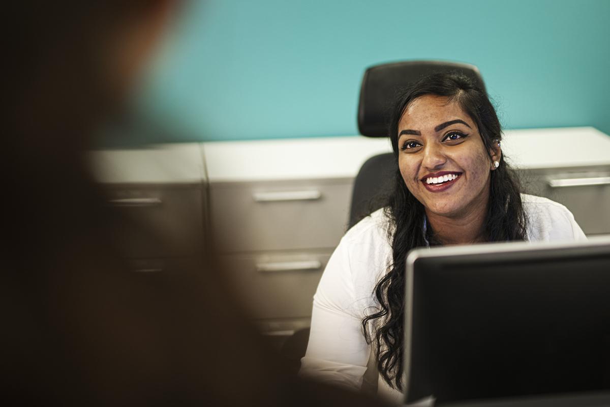 En kvinne sitter for data skjerm og hjelper med IT service til en kunde