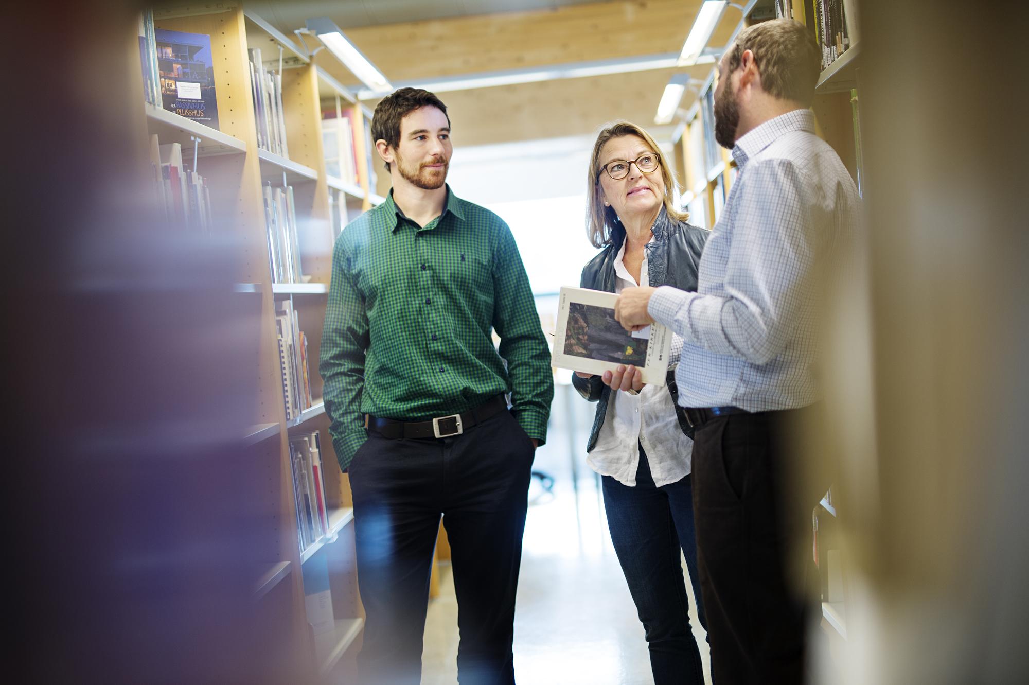 Tre kolleger i samtale mellom bokhyller