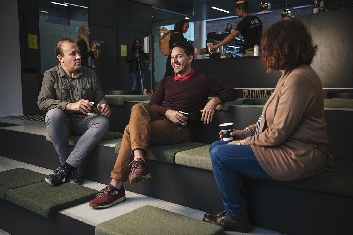 Tre kolleger i samtale i kaffebaren