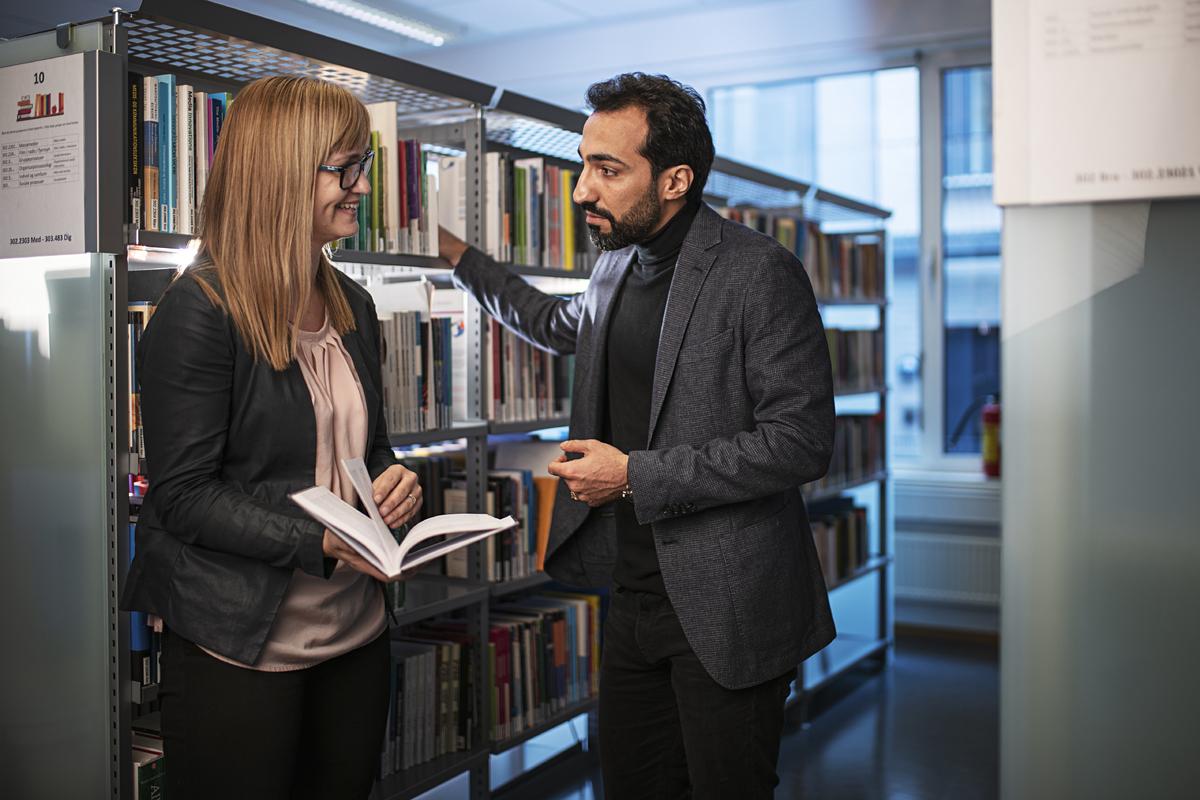 En kvinnelig og en mannlig kollega i diskusjon på biblioteket
