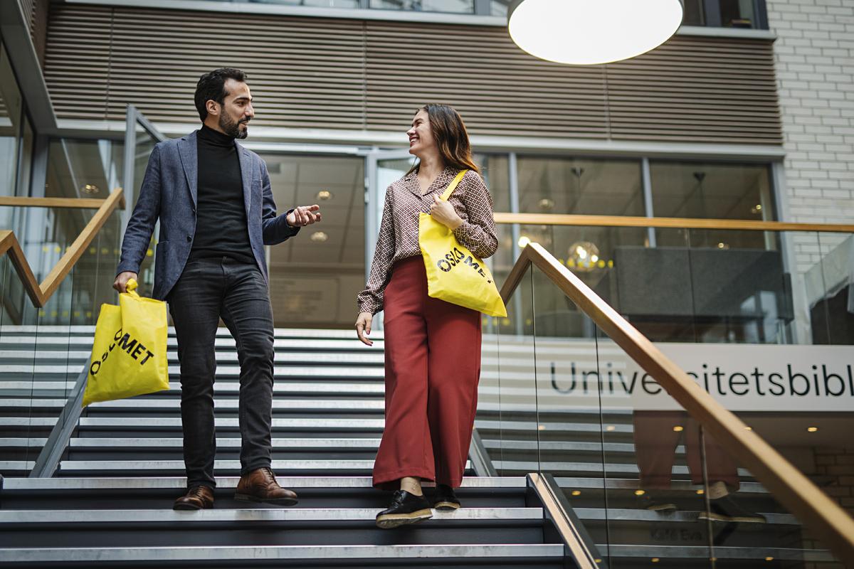 To kolleger i samtale vandrer ned trappa ved biblioteket med gule OsloMet bærenett