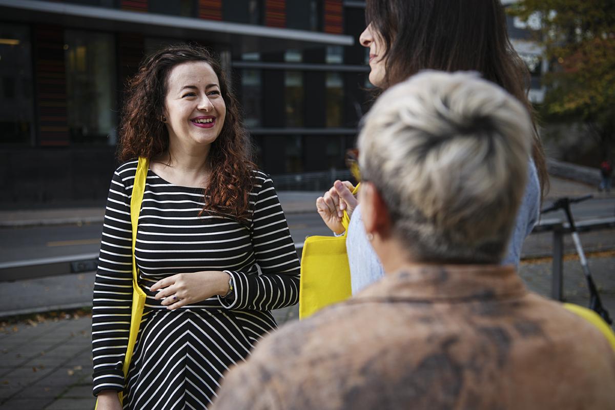 Tre kvinnelige kolleger i samtale utenfor OsloMet campus