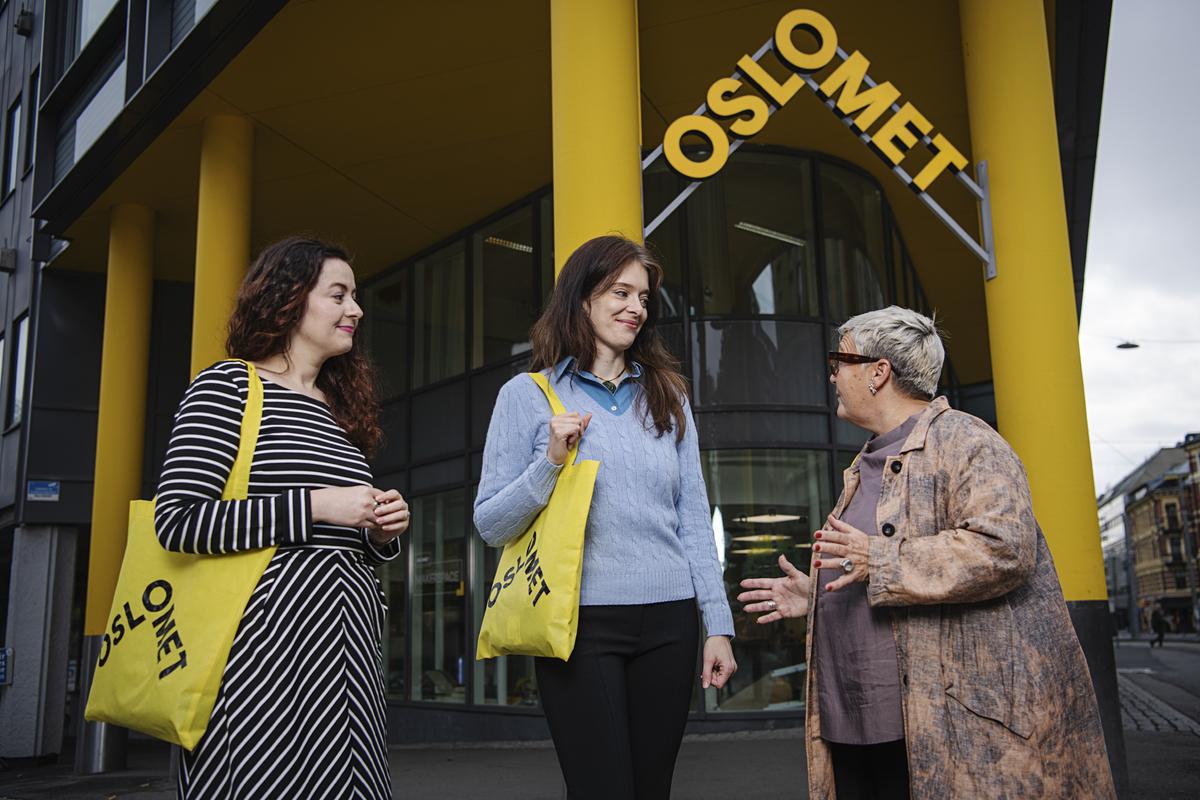 Tre kvinnelige kolleger i samtale ute foran bygg med OsloMet logo som en trekant med OsloMet i gul skrift