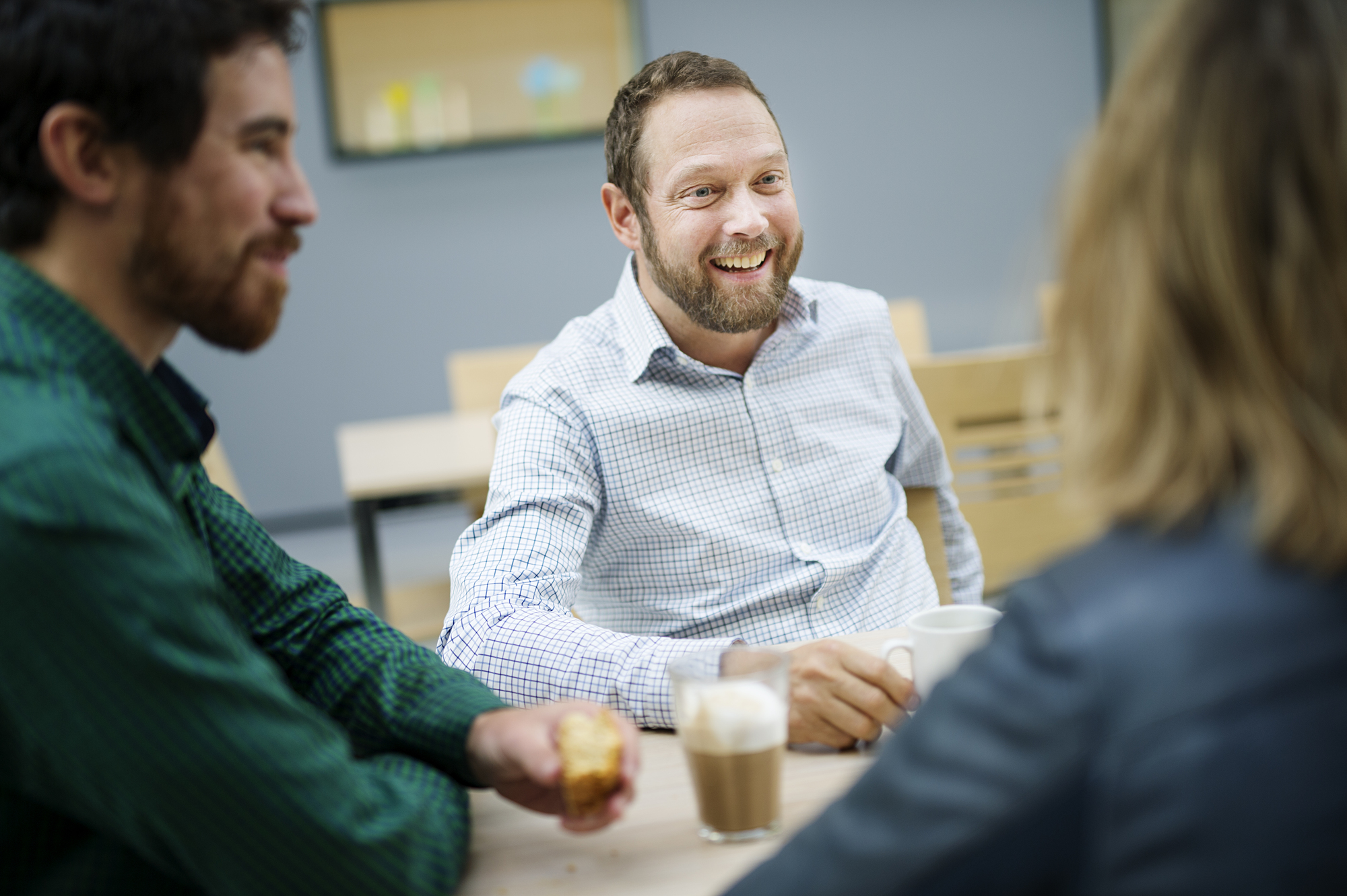 Tre kolleger i samtale over kaffe