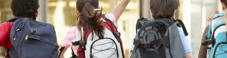 Fyra barn som sitter på rad med ryggsäckar på