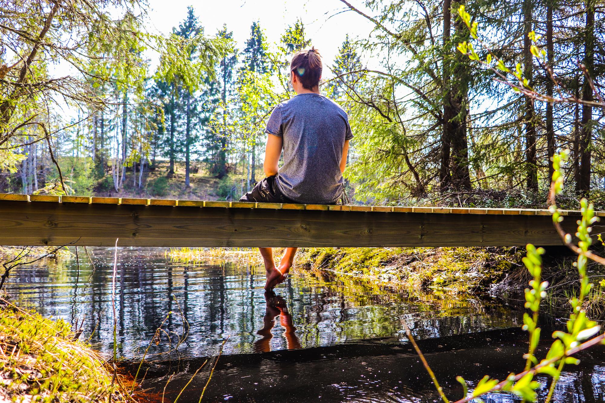 En bild från Robertsfors, en ung man sitter på en låg bro över en å, barfota med benen dinglandes över kanten