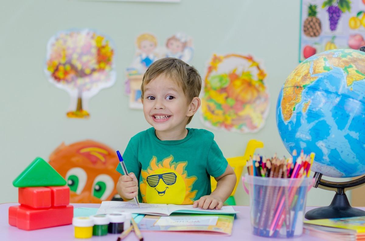 En bild på ett glatt förskolebarn som ritar