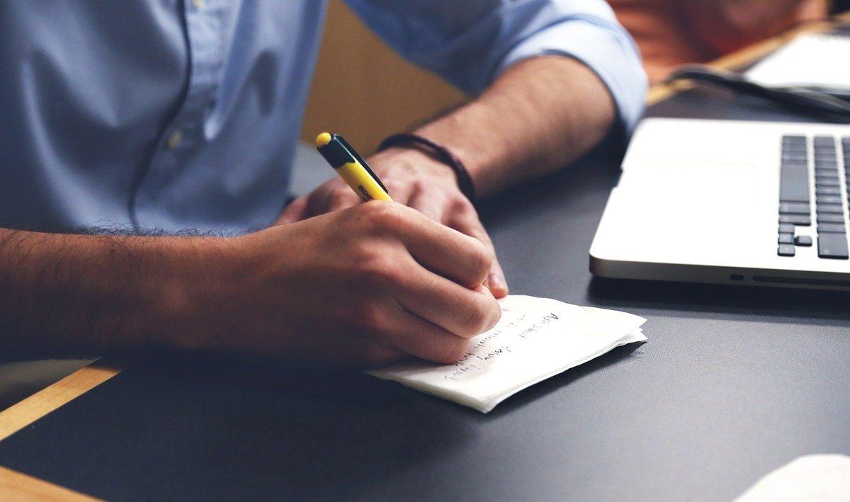 En bild på en persons underarmar, personen har en dator framför sig och skriver på ett papper