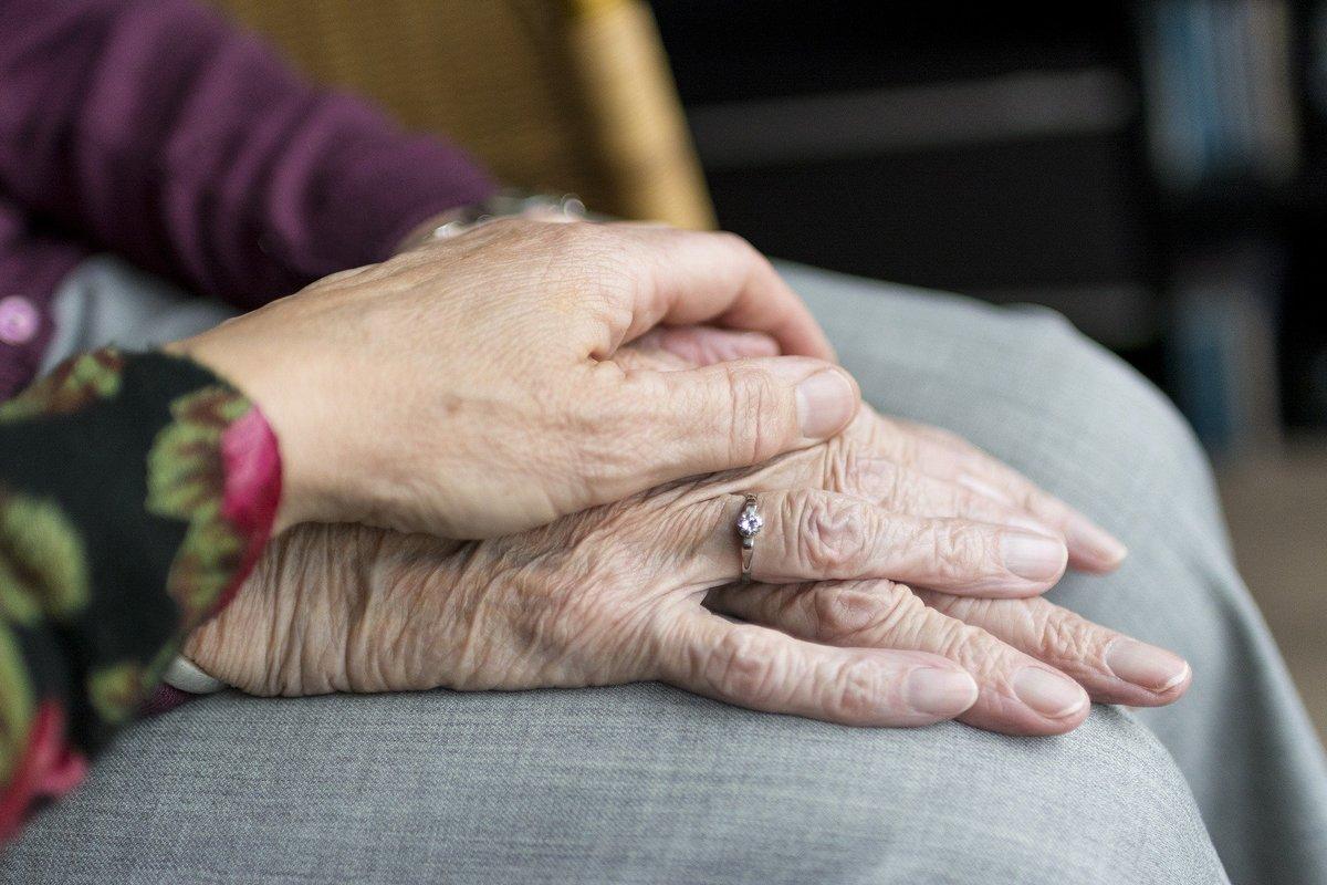 En bild på en hand som omtänksamt håller om en äldre persons händer