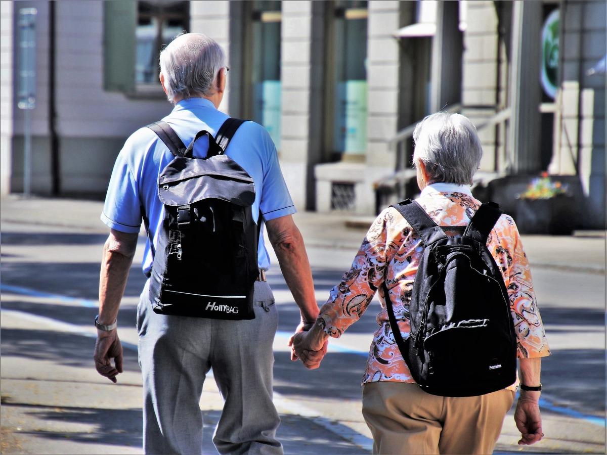 En bild på ett äldre par som promenerar hand i hand.