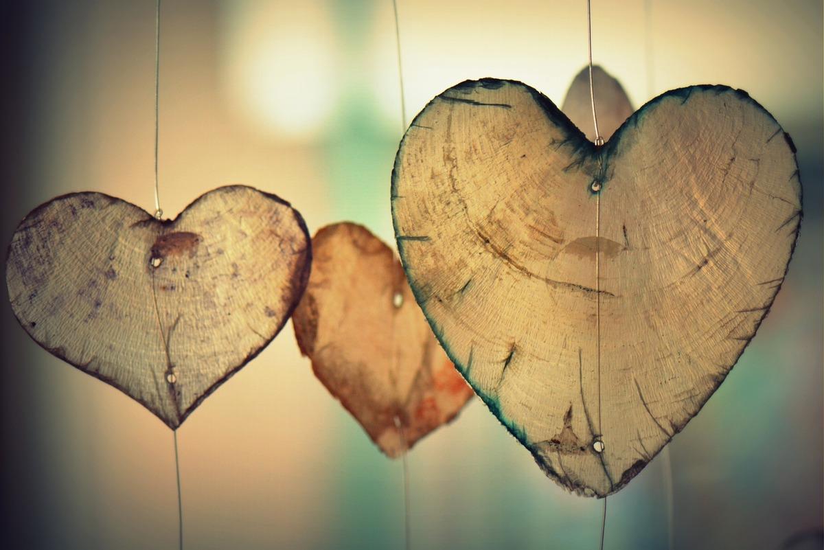 En bild på tre utsågade hjärtan i trä hängande i trådar